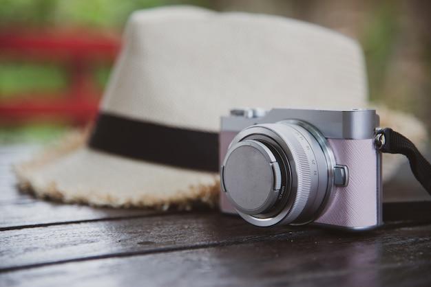 Concetto di viaggio di vista superiore con fotocamera e cappello sul tavolo