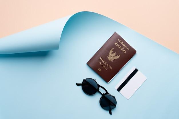 Concetto di viaggio di vista superiore con passaporto, carta di credito e occhiali da sole su priorità bassa astratta della spiaggia