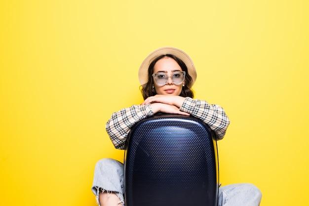 Concetto di viaggio. donna turistica felice con occhiali da sole e cappello che indossa vestiti di jeans pronti per il viaggio abbraccio valigia isolata.