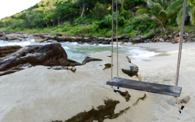 Concetto di viaggio estivo, swing sopra la spiaggia di sabbia con sfondo isola.