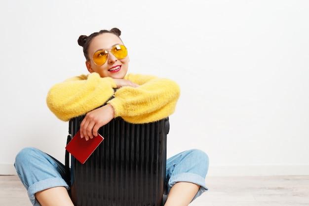 Concetto di viaggio. ragazza donna felice con valigia e passaporto