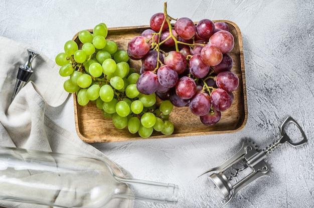 Concetto di vinificazione artigianale. uva verde e rossa. sfondo di vino.