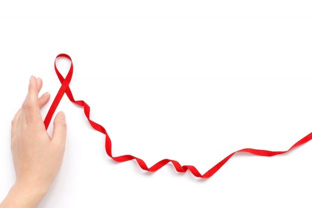 Concetto di world aids day. aid nastro rosso sulla mano della donna