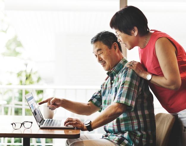 Concetto domestico anziano del computer delle coppie senior