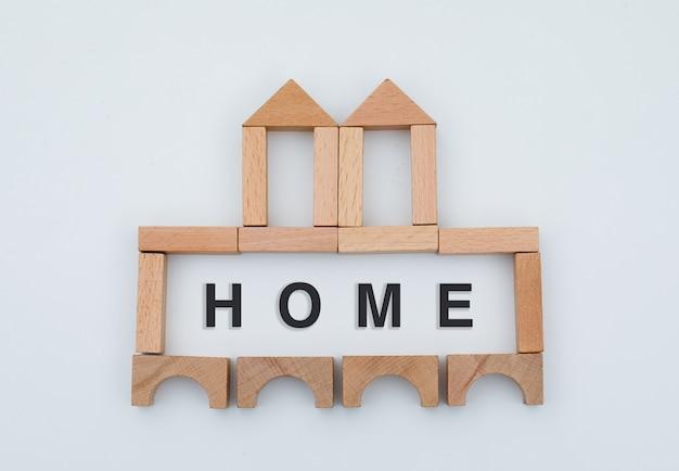 Concetto domestico con il castello di legno incompleto sulla disposizione piana del fondo bianco.