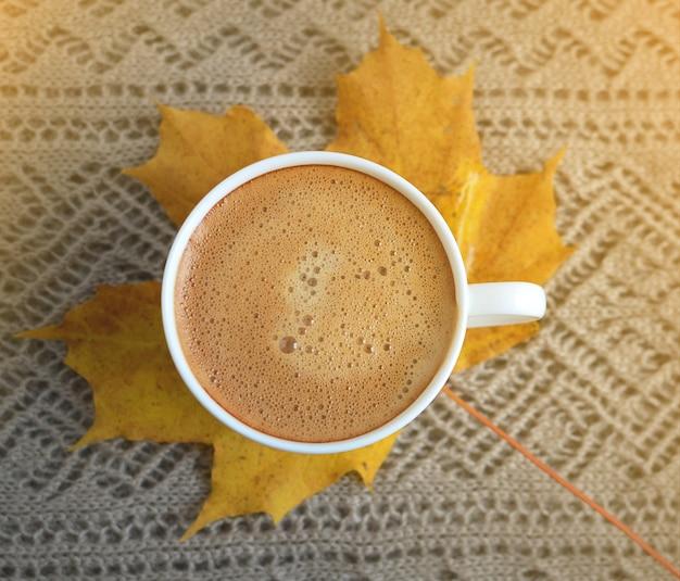 Concetto dorato autunnale di mattina di luce solare delle castagne delle foglie di acero della bevanda della tazza di caffè tonificato