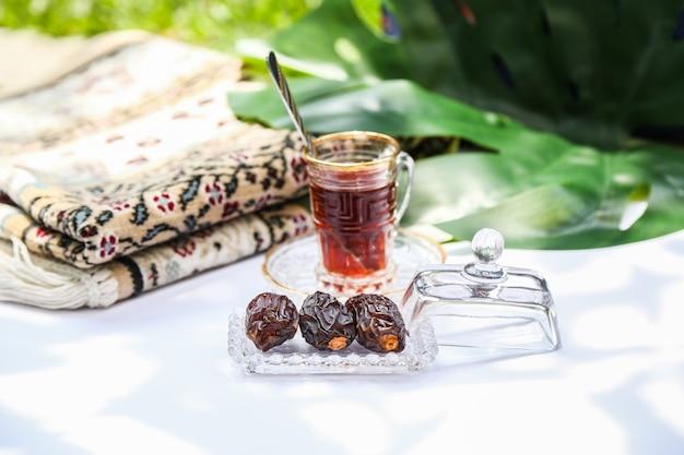Concetto e ispirazione del ramadan che mostrano alcune palme da datteri in un vassoio trasparente in uno sfondo di giardino