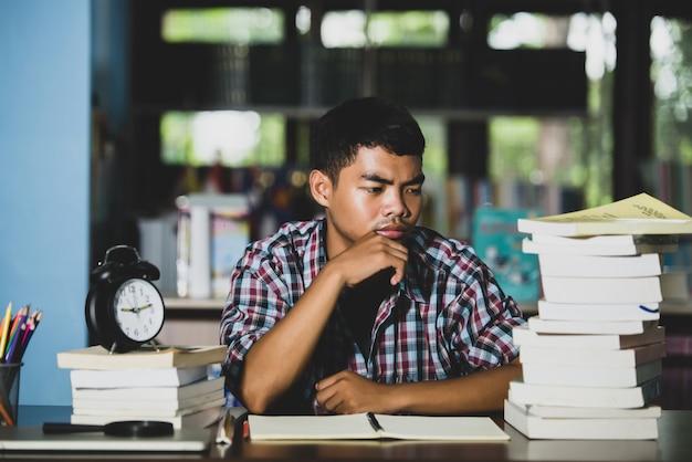 Concetto educativo: studente stanco in una biblioteca