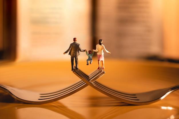 Concetto felice dell'equilibrio di vita del lavoro e della famiglia. miniatura di padre, madre e figlio che si tengono per mano e che camminano sulla forcella nel ristorante