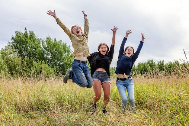 Concetto felice della gente di vacanza di vacanze estive. un gruppo di un ragazzo di tre amici e due ragazze che saltano, ballano e si divertono insieme all'aperto. fai un picnic con gli amici in viaggio nella natura.