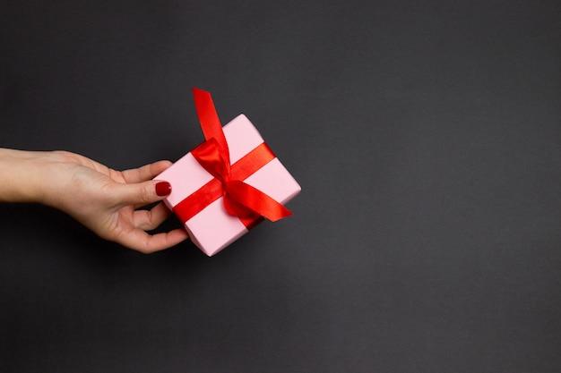 Concetto felice di feste con il regalo femminile di sorpresa della tenuta della mano con il nastro rosso dell'atlante su fondo scuro