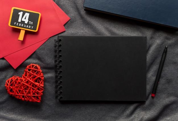 Concetto felice di san valentino, libro nero, cuore rosso e penna sul panno grigio