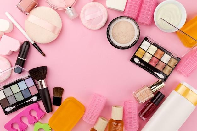 Concetto femminile beauty spa. diversi compongono cosmetici essenziali di bellezza cosmetici su fondo piatto rosa. vista dall'alto. sopra.