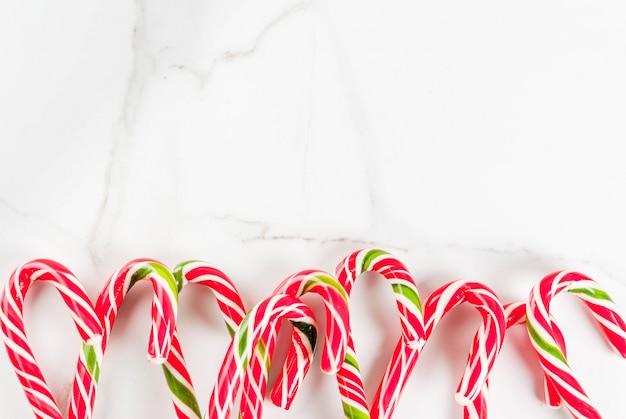 Concetto festivo di natale, un sacco di canna da zucchero candito dolci tradizionali di capodanno su un tavolo di marmo bianco. , vista dall'alto copyspace