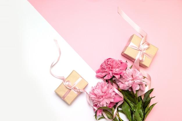 Concetto festivo di peonie e regali su bianco e rosa