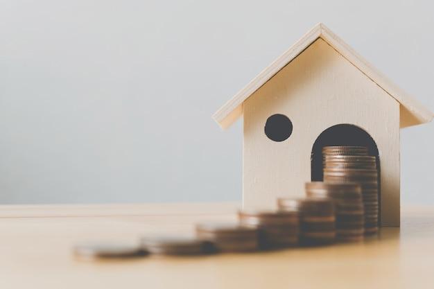 Concetto finanziario di ipoteca della casa e di investimento della proprietà, pila della moneta dei soldi con la casa di legno