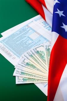 Concetto fiscale - modulo fiscale 1040, penna, denaro americano e bandiera