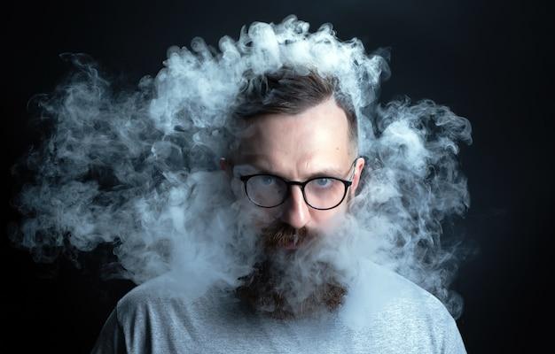 Concetto. il fumo avvolgeva il capo uomo. ritratto di un uomo barbuto ed elegante con fumo. fumo di seconda mano.