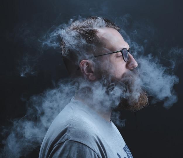 Concetto. il fumo avvolgeva il capo uomo. ritratto di un uomo barbuto ed elegante con fumo.