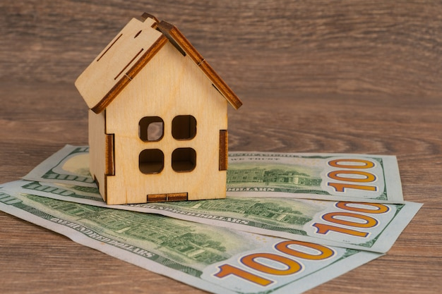 Concetto immobiliare con modello di casa in legno e banconote da 100 dollari