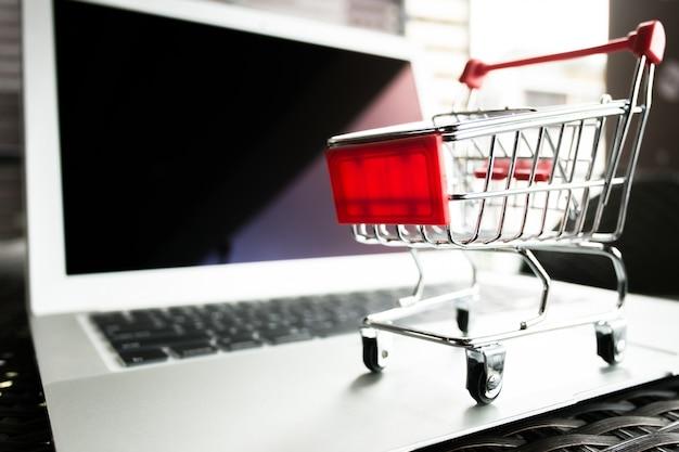 Concetto in linea di acquisto - carrello di carrello rosso sul computer portatile