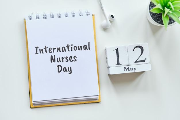 Concetto internazionale del calendario del mese del 12 maggio del giorno 12 degli infermieri sui blocchi di legno.