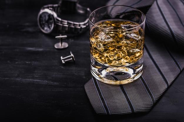 Concetto maschile per la festa del papà. cravatta, orologi, gemelli e un bicchiere di whisky con ghiaccio