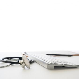 Concetto medico con stetoscopio e tastiera del computer a margine bianco.