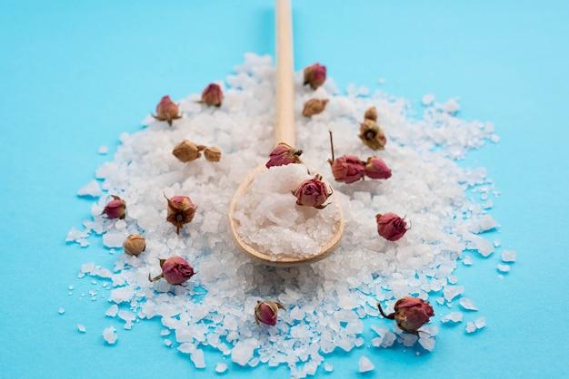 Concetto minimalista della stazione termale del sale da bagno e germogli rosa