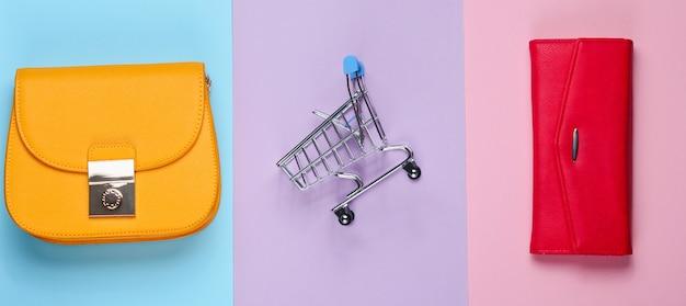 Concetto minimalista shopaholic. borsa, borsa, mini carrello della spesa. vista dall'alto