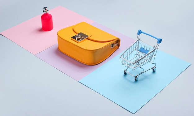 Concetto minimalista shopaholic. borsa gialla, bottiglia di profumo, mini carrello della spesa. vista laterale