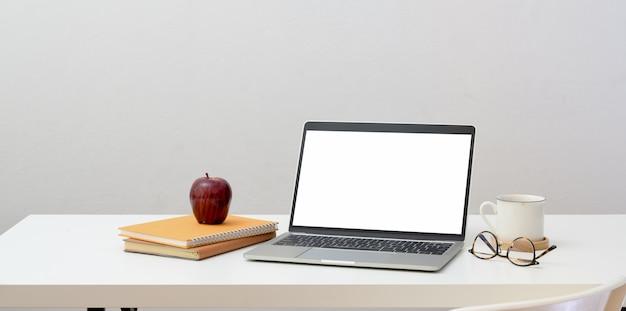 Concetto minimo del posto di lavoro con il computer portatile aperto dello schermo in bianco con gli articoli per ufficio e le decorazioni