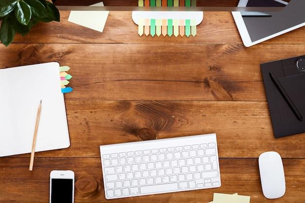 Concetto moderno del posto di lavoro di progettazione creativa, pitture del computer sulla tavola di legno marrone