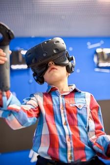 Concetto moderno di tecnologia, di gioco e della gente - ragazzo in cuffia avricolare di realtà virtuale o vetri 3d che giocano videogioco al centro di gioco