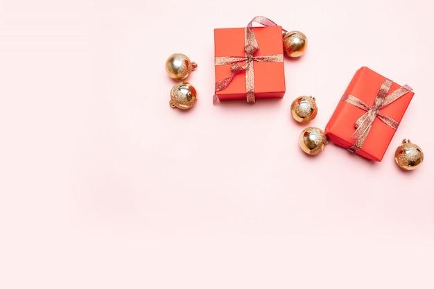 Concetto newyear minimo di natale dei contenitori di regalo rossi di natale, palle su fondo di rosa pastello. minimo concetto di capodanno.