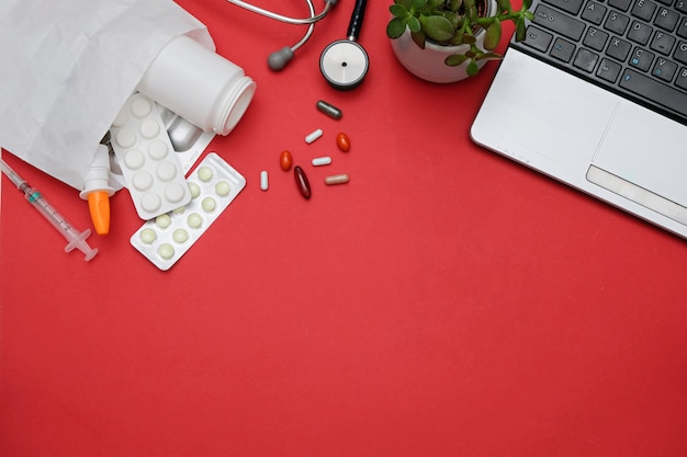 Concetto online di farmacia e farmacia. pillole e computer portatile della medicina su fondo rosso. distesi piatti, spazio per il testo