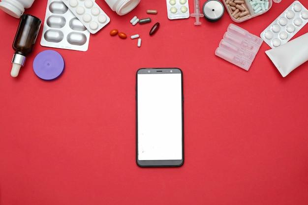 Concetto online di farmacia e farmacia. pillole e smartphone della medicina su rosso