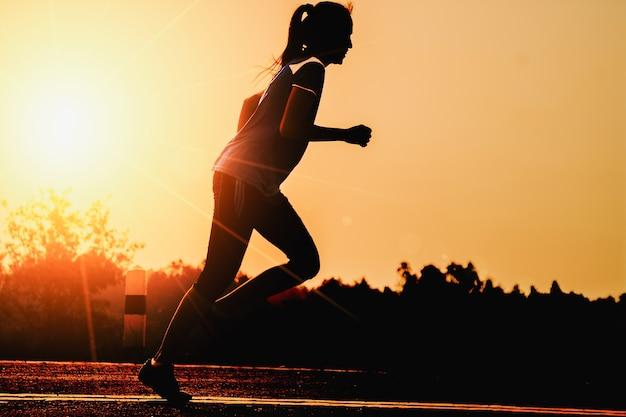 Concetto pareggiante di benessere di allenamento di alba della siluetta di forma fisica della donna.