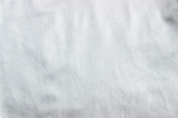 Concetto per cuoio, tessuto e struttura, primo piano di cuoio metallico grigio argento sgualcito, fondo del tessuto