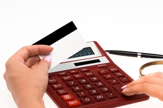 Concetto per lo shopping su internet: mani con calcolatrice e carta di credito