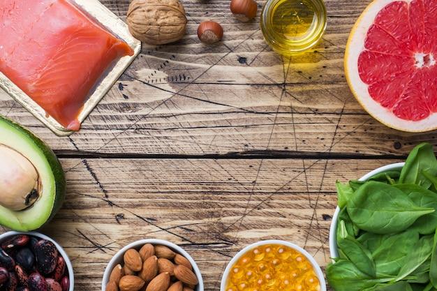 Concetto prodotti antiossidanti alimentari sani: pesce e avocado, noci e olio di pesce, pompelmo su fondo in legno. copia spazio