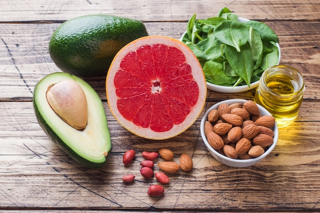 Concetto prodotti antiossidanti alimentari sani: pesce e avocado, noci e olio di pesce, pompelmo su fondo in legno.
