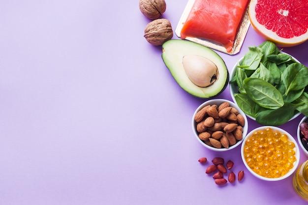 Concetto prodotti antiossidanti alimentari sani: pesce e avocado, noci e olio di pesce, pompelmo su sfondo rosa. copia spazio