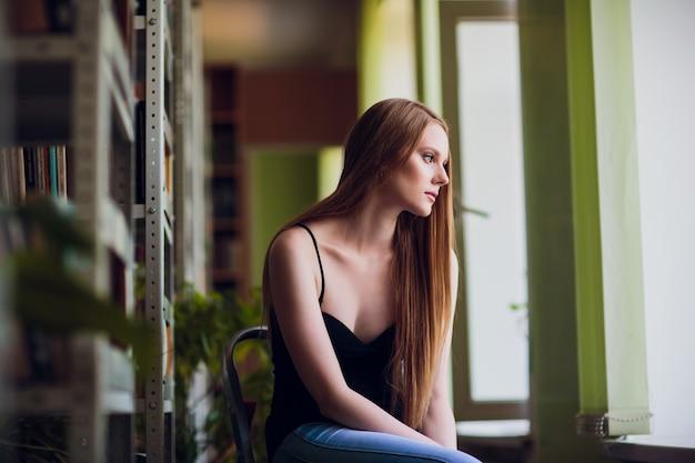 Concetto riflessivo. biblioteca donna seduta ragazza