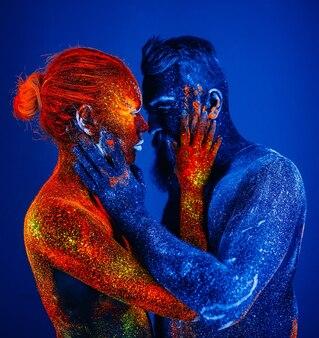 Concetto. ritratto di un uomo barbuto e una donna dipinti con polvere ultravioletta.