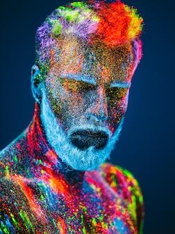 Concetto. ritratto di un uomo barbuto. l'uomo è dipinto in polvere ultravioletta.