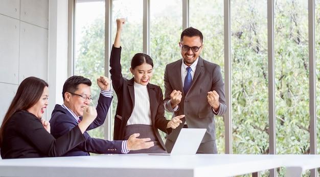 Concetto riuscito dell'uomo d'affari del gruppo. sono contenti e felici quando guardano lo schermo del laptop.