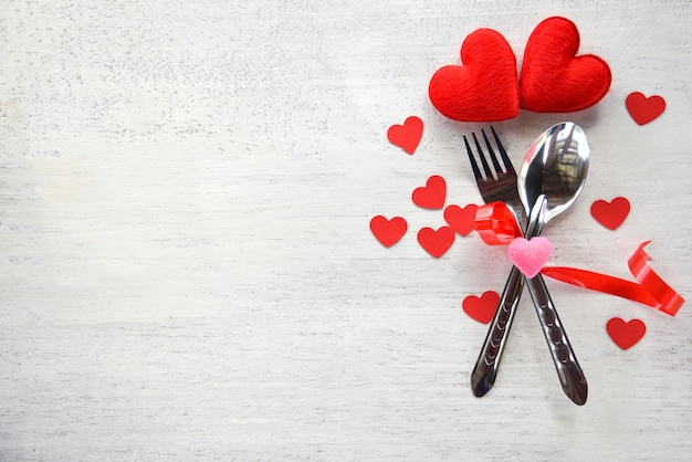 Concetto romantico di amore della cena dei biglietti di s. valentino regolazione romantica della tavola decorata con il cucchiaio della forchetta e cuore rosso su di legno bianco