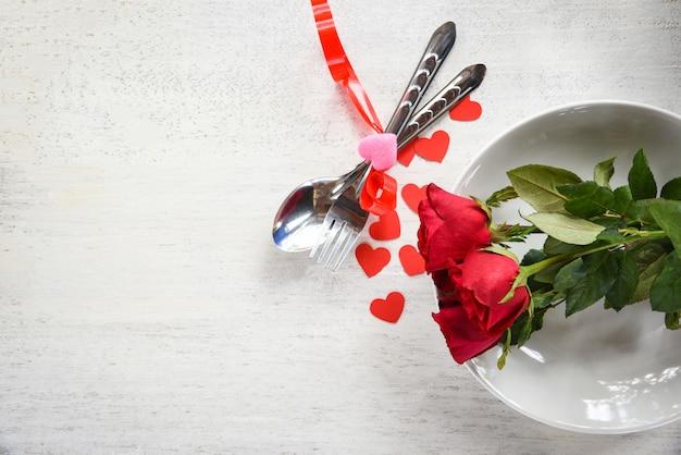 Concetto romantico di amore della cena dei biglietti di s. valentino regolazione romantica della tavola decorata con il cuore e le rose rossi del cucchiaio della forchetta sul piatto