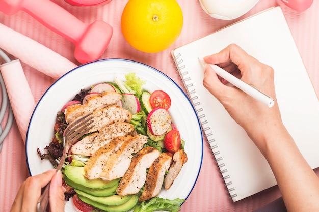 Concetto sano con cibo nutrizionale nella scatola del pranzo e attrezzature per il fitness con tempo di scrittura della donna per ottenere una buona salute sul libro del diario